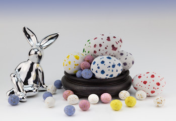 Easter egg background with silver rabbit and speckled Easter eggs on white