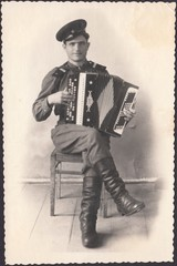 Scanned photo Russian soldier plays the accordion,circa 1955.