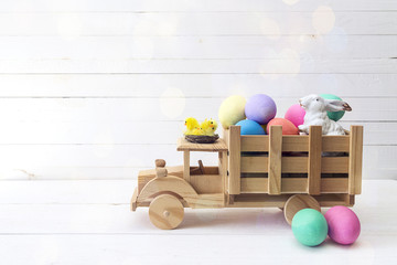 Wooden toy truck with Easter eggs and a rabbit in the back.  Space for text.