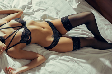 Sexy woman in bed in the morning showing her beautiful body.
