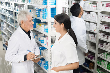Chemist Looking At Coworker While Writing On Clipboard