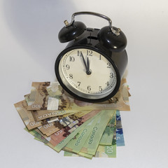 Clock on pile of Canadian Money