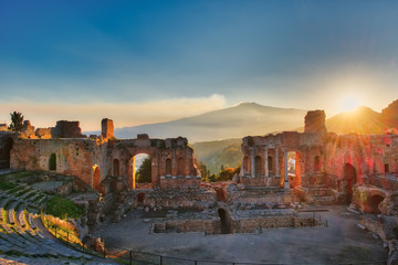 Particular of Ancient theatre of Taormina with Etna erupting volcano at sunset Wall mural