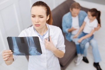 Worried distinguished specialist examining little patients x-ray