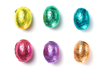 Chocolate easter eggs wrapped in multi colored foil isolated on white background