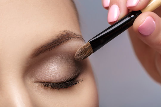 makeup artist apply makeup brush for eyes. makeup for young girl. brown eye shadow. close up