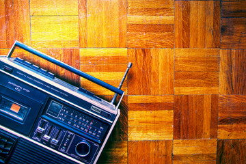Retro cassette tape recorder on wooden floor, grunge ghetto blaster, old radio player with antenna, vintage audio style