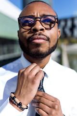 Young stylish man setting tie