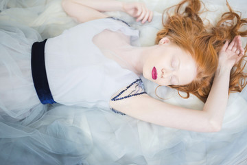 Young red-haired woman in dress on floor with eyes closed