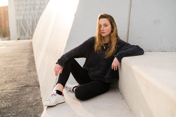 Outdoors portrait of young girl on concrete stairs looking at camera.