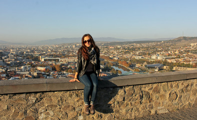 Traveler girl wearing black leather jacket sitting on the stone wall. Panoramic view of old Tbilisi, Georgia at the background. The view from the castle Narikala.