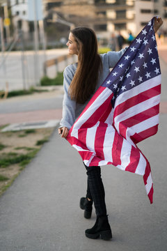 Cheerful young woman walking on street with American flag