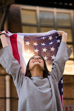 Cheerful young woman with American flag standing outdoors