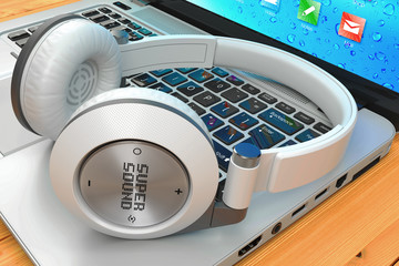 Wireless headphone and laptop on wooden table