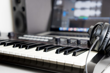Synthesizer keyboard and headphone lying on Music studio working desktop