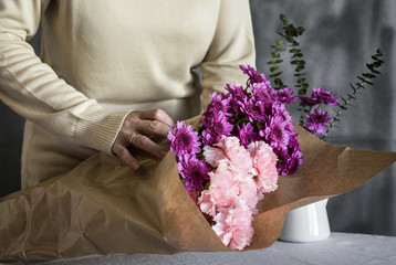 Graceful hands of the woman florist making bouquet of flowers