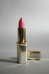 Pink lipstick in a golden tube on a gray background