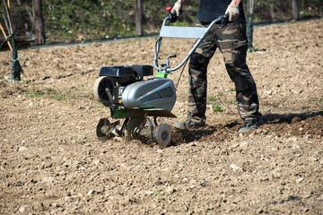 Man tilling or hoeing soil for planting