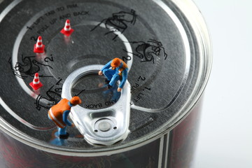 The miniature figure model of worker on aluminum can lid represent the food packaging business  concept related idea.