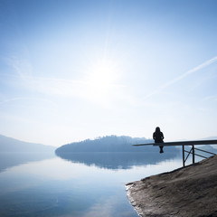 Enjoying nature, self-reflection. Woman sitting on the shore of the lake. Clear sunny day.