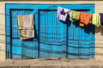 Blue window shutters with hanging laundry, Dhulkihel, Nepal