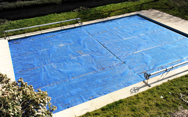 Swimming pool protected with a blue tarp in autumn