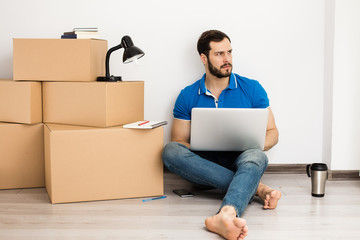 man lying on the floor with packing boxes