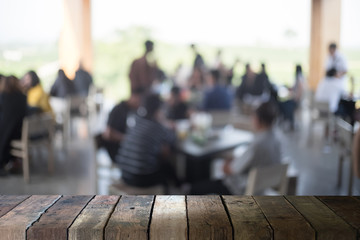 image of wooden table in front of abstract blurred background of coffee shop cafe
