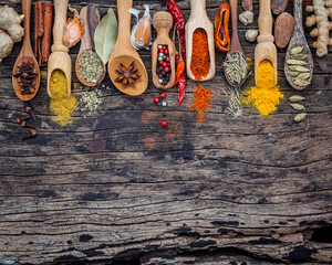 Various of spices and herbs in wooden spoons. Flat lay of spices ingredients chilli ,pepper corn, garlic, thyme, oregano, cinnamon, star anise, nutmeg, mace, ginger and bay leaves on shabby wooden..