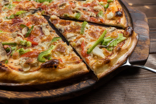 Delicious pizza with mushrooms - thin pastry crust isolated at wooden background on wooden desk