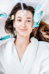 Beautiful woman with cosmetology tools lying on the medical couch. Facial treatment concept