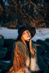 Portrait of a young beautiful blonde woman with hat, in a fur coat, outside, on the snow. A good dark day with beautiful shadows - a sunny winter day, sunset.