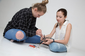 Cute and absorbed teenage girls sitting on the floor mounting a little metal helicopter model