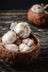 Fresh organic garlic in a clay bowl on a black wooden background. Close up and selective focus. Toned image