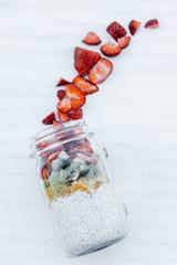 Flat photo Chia seed pudding with Strawberry, kiwi, orange served in a Mason Jar on white background