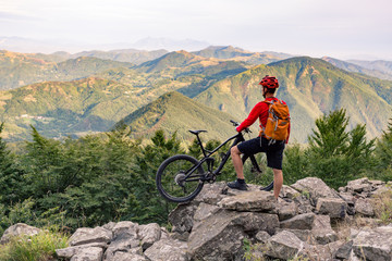 Mountain biker looking at view on bike trail in autumn mountains.