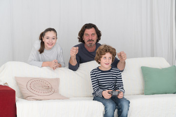 Happy family having fun playing computer console game at home