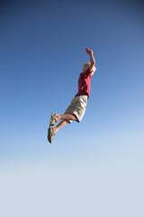 Blonde young boy jump high up