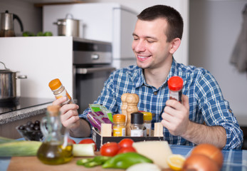 guy chooses spices in the kitchen at home