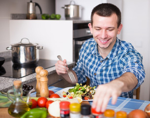 young man chooses spices in kitchen at home