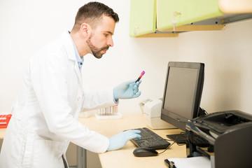 Doctor adding blood sample to database