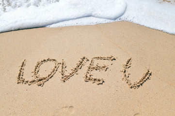 Love U sign on the sand beach copy space texture background