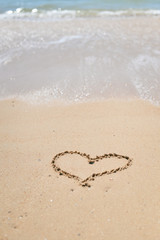 Love heart sign on the wet beach sand sea wave background