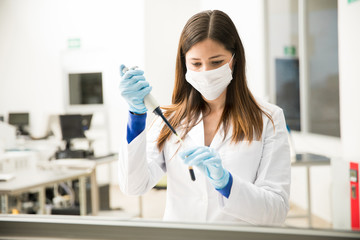 Female chemist using a pipette