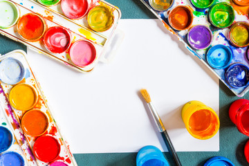 Artistic paint brushes and water color on a dark background