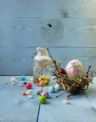 Easter composition. Porcelain Easter egg in the nest, a jar for sweets with bunny, colorful candy.