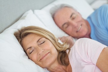 Senior couple resting on bed