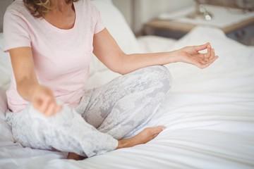 Senior practicing yoga on bed