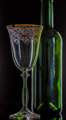 Red Wine Glass And Empty Wine Bottle On Black Background