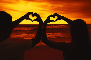 Liebespaar malt Herzen in den Abendhimmel